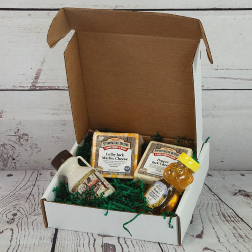 Gift box including cheeses, maple syrup, and honey.